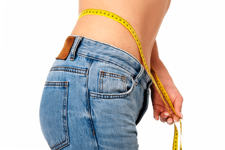 Healthy lifestyle concept - woman in blue jeans measures her perfect waistline with a measuring tape in close-up Stock Photo