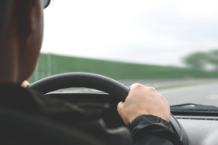 Close-up on male hands on the steering wheel of a car on a blurred background of the highway (reduced tone effect)