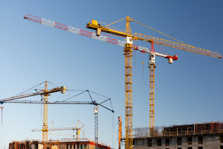 Group of construction cranes on a blue sky background. Stock Photo