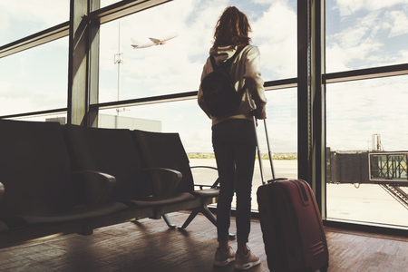 Vacation travel concept - rear view of a young girl with a suitcase waiting for the departure of her plane on the background of the airport ( vintage effect)