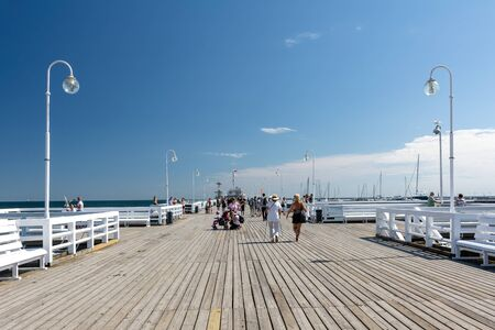 Sopot, Poland - July 27, 2018: Tourists walking on wooden Sopot Pier in a sunny day. It is the longest wooden pier in Europe and is located on the coast of Baltic Sea.