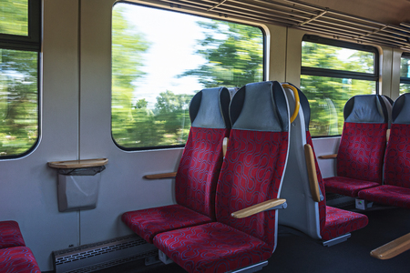 Interior view of an empty passenger wagon in a moving train.