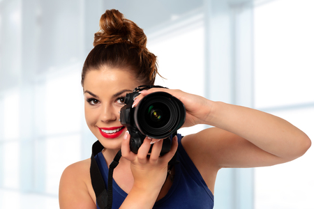 Photographer occupation concept - beautiful and attractive woman holding a professional DSLR camera and smiling in the photo studio