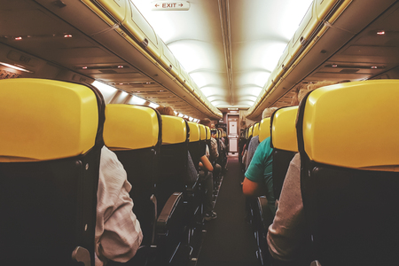 Interior view of a passenger airplane in an economic class during the flight ( vintage effect).