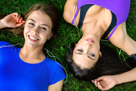 Top view of two beautiful and young girls resting on the grass after outdoor workout on a sunny day Stock Photo