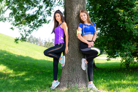 Two beautiful and young girls resting in a park leaning against a tree after a workout on a sunny day