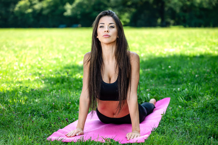 Beautiful young woman doing yoga exercises in the park on a sunny day Stock Photo