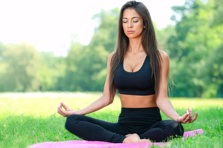 Attractive and young woman doing yoga meditation in a lotus pose outdoors in a park on a sunny day