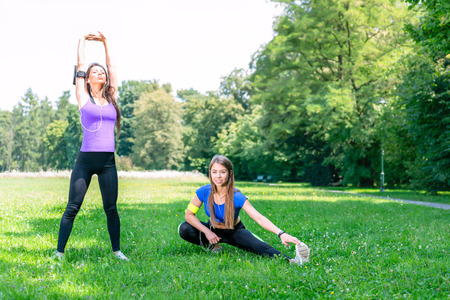 Healthy lifestyle concept - two young and fit girls stretching before jogging on the grass in a park on a sunny morning.