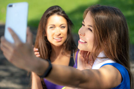 Millennials lifestyle concept - two sports girls taking a selfie and smiling after outdoors training on a sunny day. Stock Photo