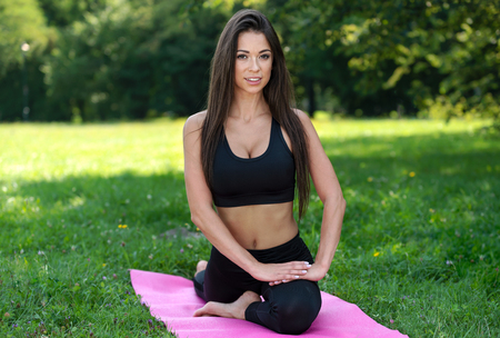 Beautiful young woman doing yoga outdoors exercises in the park on a sunny day