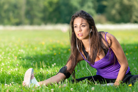 Portrait of a beautiful young girl stretching before jogging on the grass in the park on a sunny morning. Stock Photo