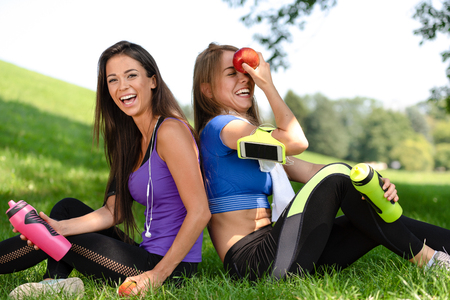 Portrait of two cute girls relaxing and smiling after outdoors exercises in the park on a sunny day