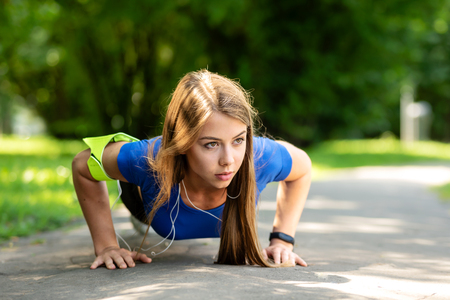 Fitness and healthy lifestyle concept - cute girl doing push-up exercise on the park in a sunny morning in close-up