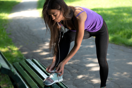 Fitness woman tying laces in running shoes during outdoors workout in the park on a sunny morning Stock Photo