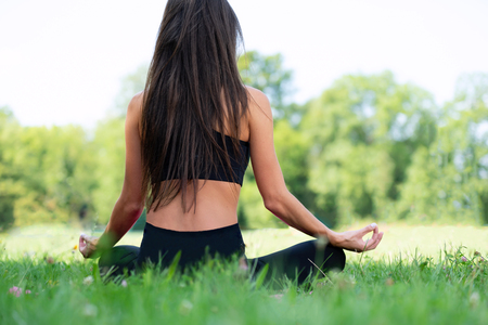 Back view of a young woman doing yoga meditation in a lotus pose outdoors in a park on a sunny day