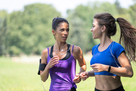 Two beautiful and attractive fitness girls are jogging in the park on a sunny morning