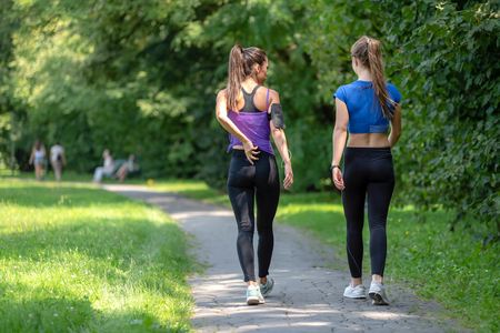 Back view of two attractive fitness girls going on a jogging in a public park on a sunny morning