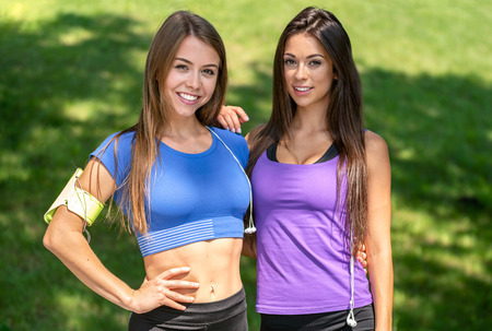Portrait of two beautiful active girls resting and smiling after outdoors training on a sunny day in the park