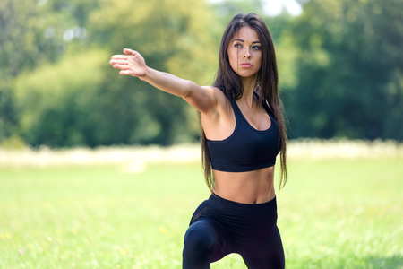 Beautiful young woman doing outdoors yoga exercises in the park on a sunny day
