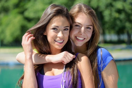 Portrait of two beautiful fitness girls resting and smiling after outdoors training on a sunny day day in a public park.
