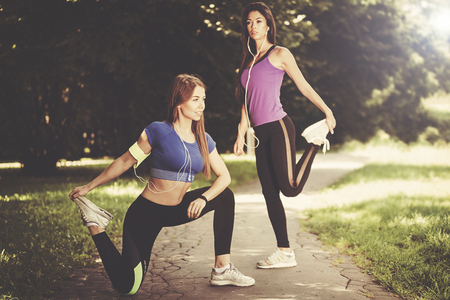 Two young and fit girls stretching before jogging in the park on a sunny morning (vintage effect)