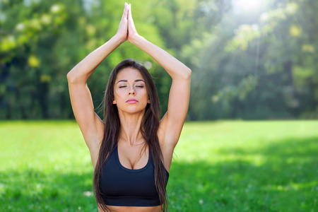 Portrait of attractive and young woman with close eyes doing outdoors yoga meditation in a park on a sunny day Stock Photo