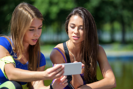 Young attractive fitness girls talking about their workout and checking sport application details on the smartphone