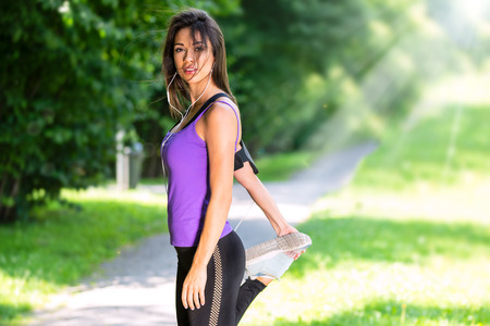 Portrait of a beautiful young girl stretching before jogging in the park on a sunny morning (copy space)