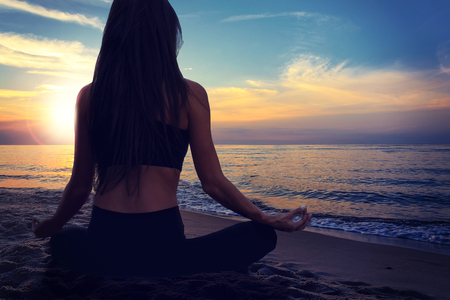 Back view of a young woman doing yoga meditation in a lotus pose at the seacoast on a sunset background.
