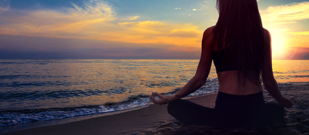 Yoga meditation banner - woman in a lotus pose on a seaside beach on a background of a picturesque sunset landscape (copy space) Stock Photo