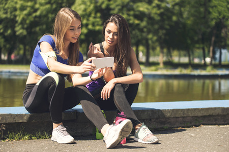 Young attractive fitness girls talking about their workout and checking sport application details on the smartphone (vintage effect) Stock Photo