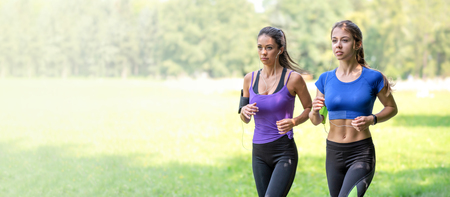 Healthy lifestyle banner - two beautiful fitness girls are jogging in the park on a sunny morning (copy space) Stock Photo