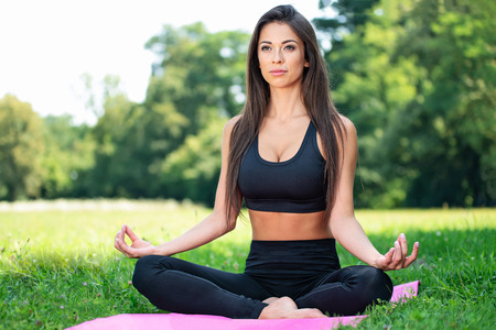 Beautiful young woman doing outdoors yoga exercises in a lotus pose in the park on a sunny day Stock Photo