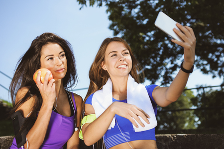 Millennials lifestyle concept - two sports girls take a selfie and smile while training outdoors on a sunny day ( vintage effect) Stock Photo