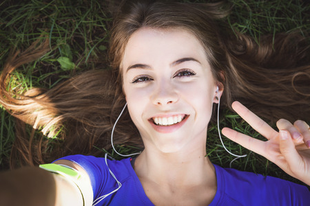 Beautiful fitness girl taking a selfie photo and showing victory gesture while resting after outdoors workout (vintage effect)