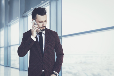 Trendy and fashionable businessman walking inside the corporate building and talking on the phone (mixed)