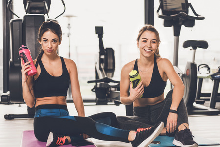 Two happy and cute girls resting after workout at the gym Stock Photo
