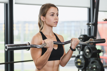 Cute girl has a hard athletic workout in the gym, doing exercises with barbells.