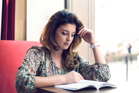 Beautiful and sensual young woman reading a book next to a window in a restaurant or coffee bar.