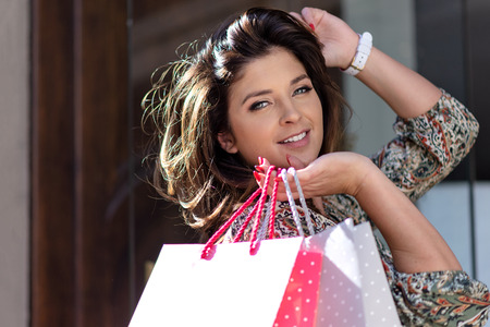 Happy young woman with shopping bags is looking at camera and smiling while doing shopping in the city Stock Photo
