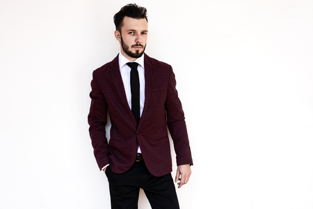 Handsome and elegant fashionable man or businessman posing a white background