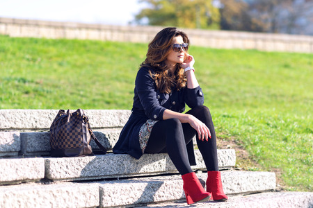 Beautiful young fashionable woman with a nice hairstyle and sunglasses sitting on the stairs and resting outdoors on a sunny day. Stock Photo