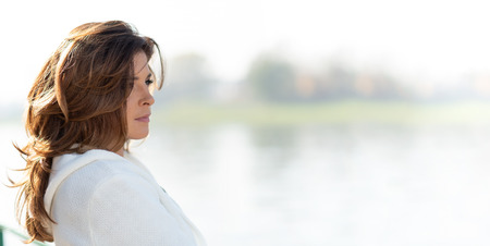 Beautiful and sensual woman is looking thoughtful at the idyllic landscape of the coast or river in the city illuminated by deep morning light (copy space)