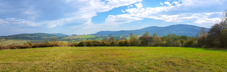 Wide panorama of idyllic autumn mountains landscape on a sunny day in the morning. Stock Photo