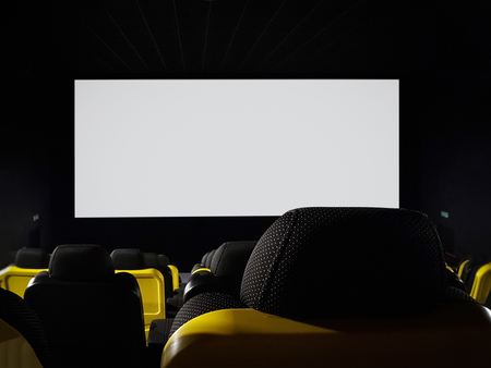 Mock-up of an empty cinema hall with blank white screen to add advertisement (copy space)