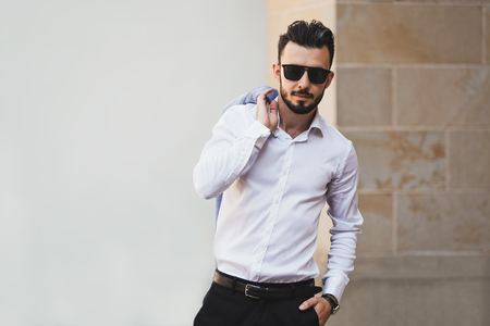 Portrait of elegant and fashionable man in black sunglasses posing on the street Stock Photo