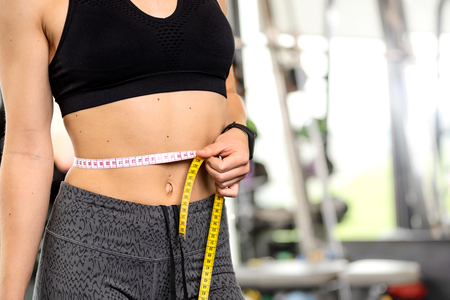 Healthy lifestyle concept - woman after workout at the gym measures her perfect waistline with a measuring tape in close-up