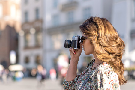 Vacation photographer concept - beautiful and attractive woman holding a retro SLR camera and shooting famous landmarks of a historic city (copy space) Stock Photo