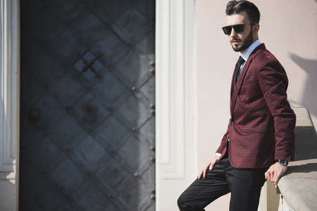 Elegant fashionable man in black sunglasses posing outdoor on the stairs (copy space).